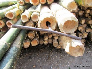 A metal rod is used to puncture through the bamboo pole to prepare it for treatment
