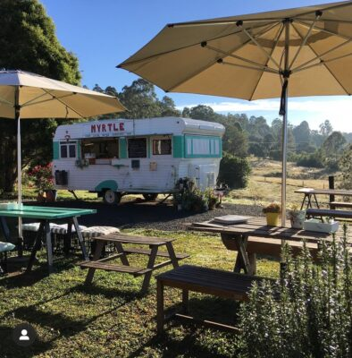 Vintage green and white caravan in scenic farm setting