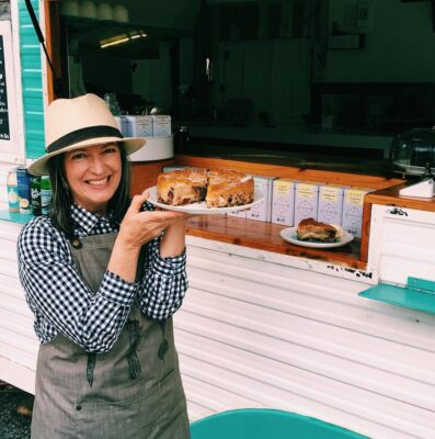 Sally holds up a tray of baked goods in front of food van