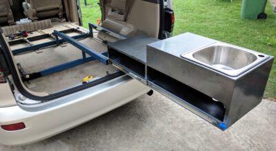 Shows slide out sink at back of van