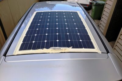 Looking down on the roof as solar panel is glued on